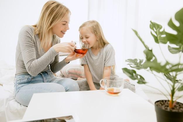 Jovem mãe e sua filha em casa na manhã ensolarada. cores pastel suaves. tempo feliz para a família no fim de semana. conceito de dia das mães
