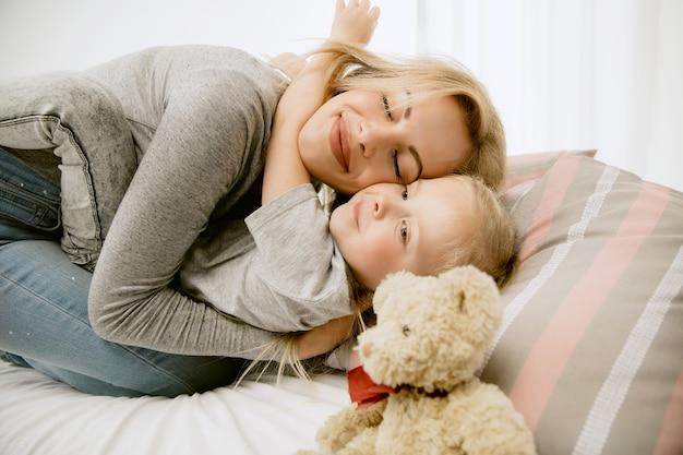 Jovem mãe e sua filha em casa na manhã ensolarada. cores pastel suaves. tempo feliz para a família no fim de semana.