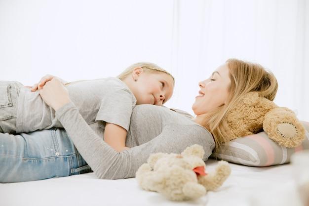 Jovem mãe e sua filha em casa na manhã ensolarada.
