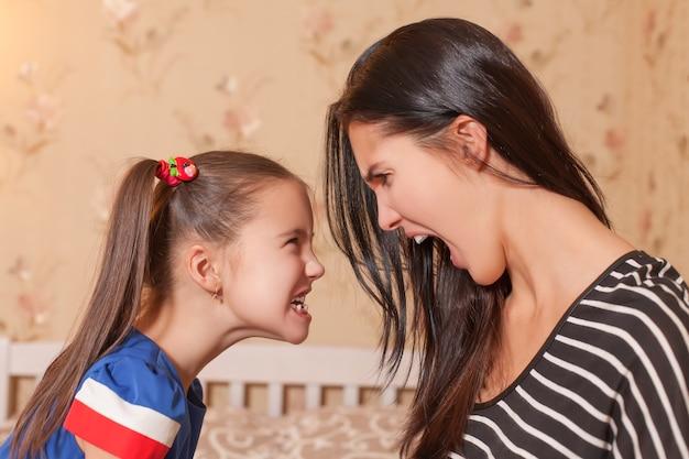 Jovem mãe e sua filha fazem uma para a outra caretas terríveis