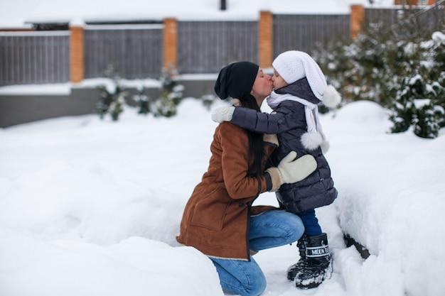 Jovem mãe e sua filha feliz se divertindo ao ar livre em dia ensolarado de inverno