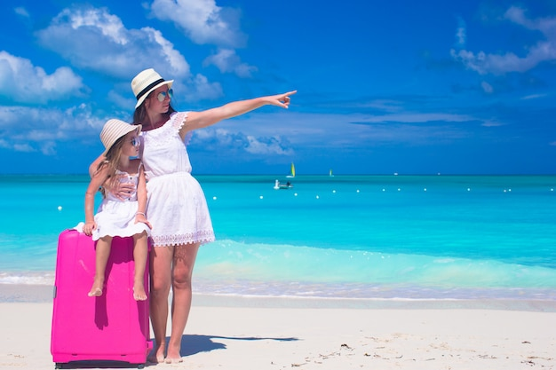 Jovem mãe e sua filha pequena com bagagem na praia tropical branca