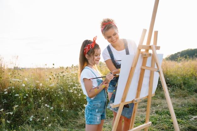 Jovem mãe e sua filha se divertem. mãe sorridente com linda filha desenha a natureza