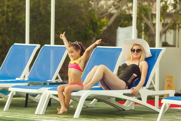 Jovem mãe e sua filha se divertir perto da piscina