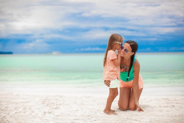 Jovem mãe e sua filhinha bonitinha sussurrando na praia branca