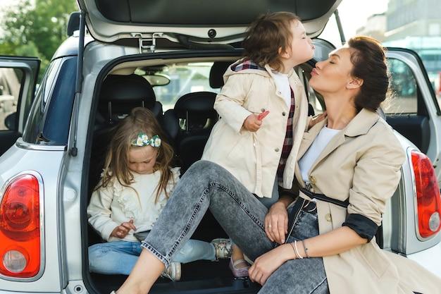 Jovem mãe e suas adoráveis filhas sentadas no porta-malas de um carro.