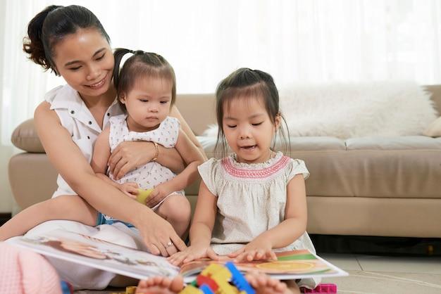 Jovem mãe e suas duas filhas pequenas olhando fotos coloridas em um livro