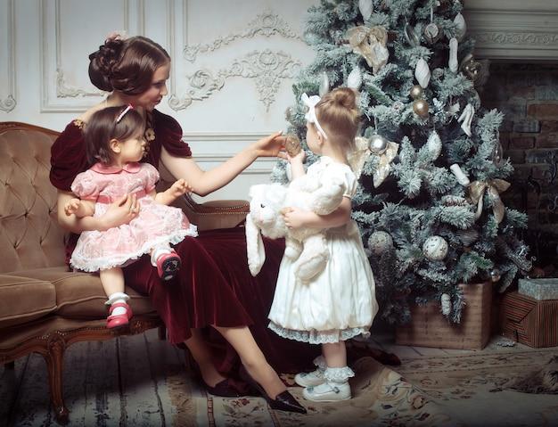 Jovem mãe e suas duas filhas pequenas perto de árvore de natal