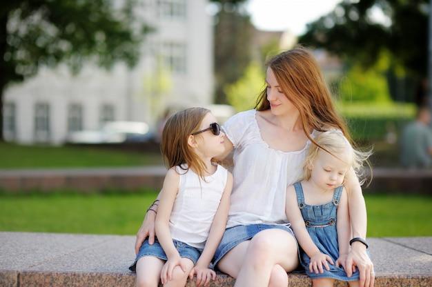 Jovem mãe e suas filhas ao ar livre no verão