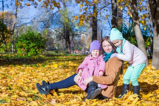 Jovem mãe e suas filhas fofos no outono park no dia quente e ensolarado