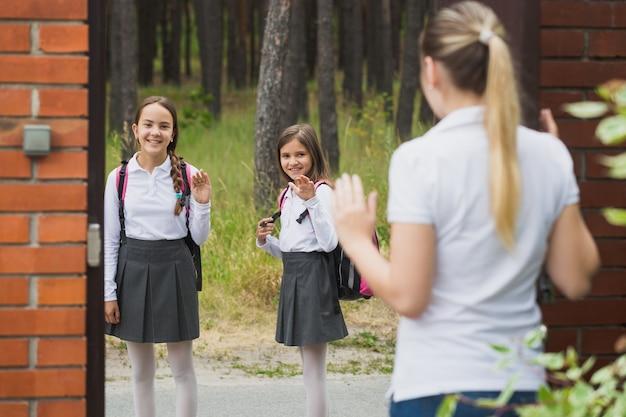 Jovem mãe em pé no quintal de casa acenando para as filhas caminhando para a escola