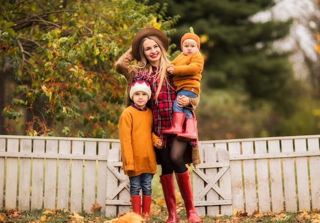 Jovem mãe em um casaco de lã marrom abraça seu filho e filha no parque outono