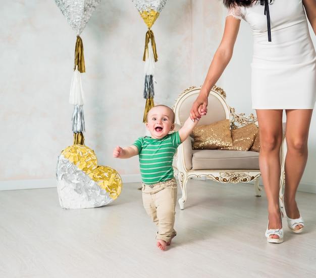 Jovem mãe em um vestido branco andando uma criança