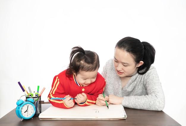 Jovem mãe ensina filha a pintar
