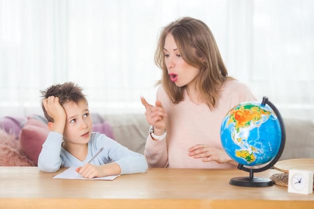 Jovem mãe ensinando seu filho pequeno em casa. mãe e filho estudando geografia dentro de casa