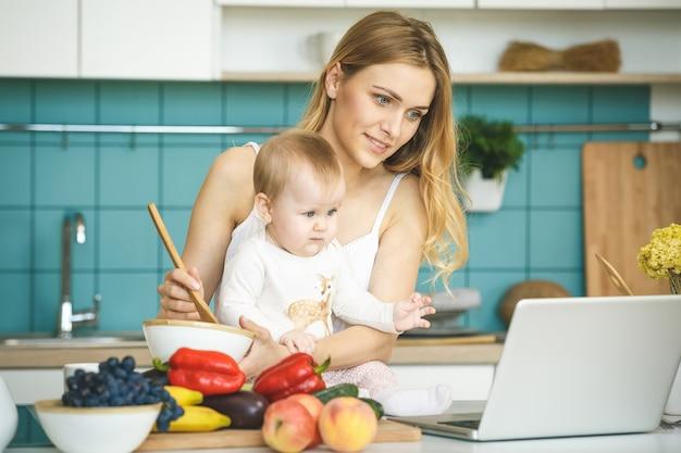 Jovem mãe está cozinhando e brincando com sua filha bebê em um ambiente de cozinha moderna. olhando para o laptop, sorrindo.