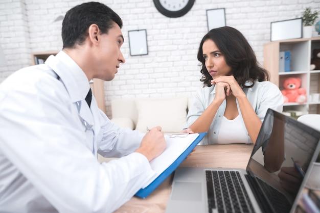 Jovem mãe está falando com um médico no consultório do seu médico.