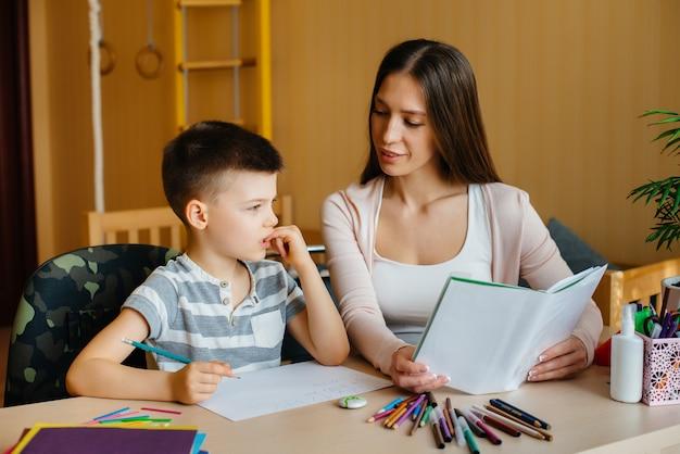 Jovem mãe está fazendo lição de casa com a casa dela
