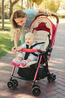 Jovem mãe falando com um bebê sorridente no carrinho rosa. pais caminhando ao ar livre com a criança