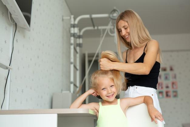 Jovem mãe faz o cabelo da filha