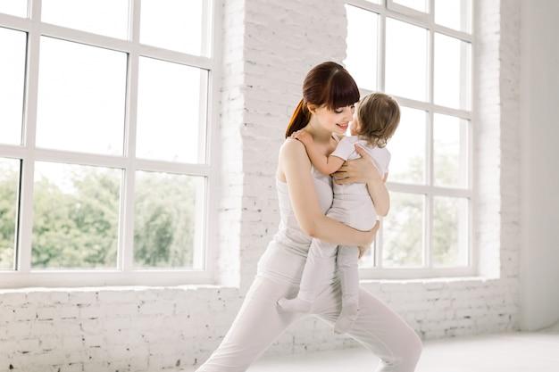 Jovem mãe faz yoga físico junto com seu bebê. mãe com bebê fazendo exercícios de ginástica e fitness