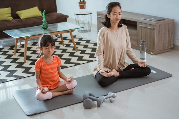 Jovem mãe fazendo exercícios de ioga em casa com a filha
