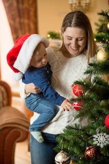 Jovem mãe feliz abraçando seu filho no boné do papai noel na árvore de natal na sala de estar