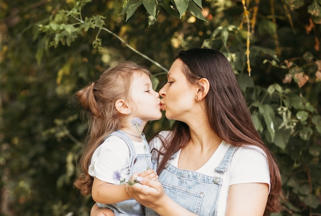 Jovem mãe feliz beija sua filhinha na natureza no verão