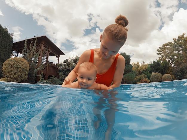 Jovem mãe feliz brincando com seu bebê na piscina em um dia quente de verão