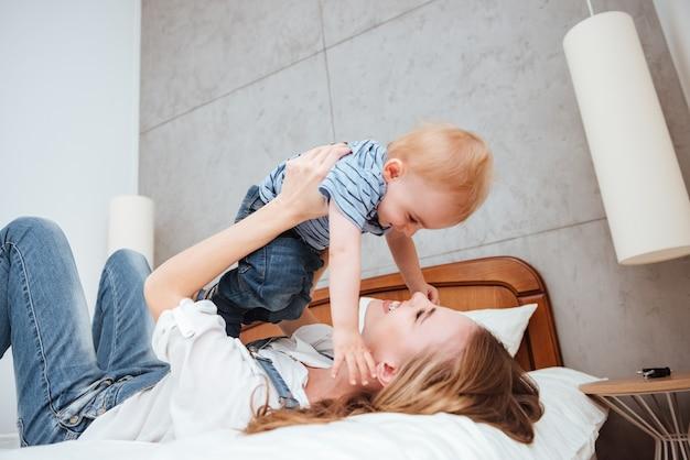 Jovem mãe feliz brincando e se divertindo com seu filho na cama em casa