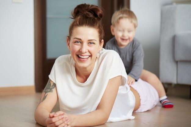 Jovem mãe feliz com filho pequeno em casa