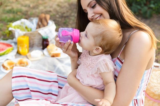 Jovem mãe feliz com sua filha no parque Foto Premium