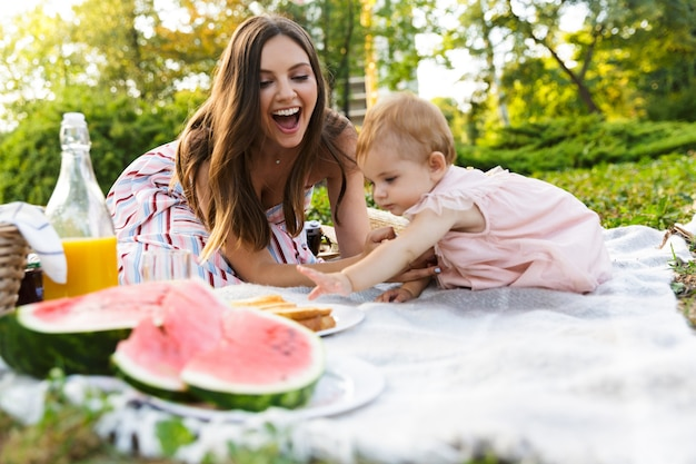 Jovem mãe feliz com sua filha no parque
