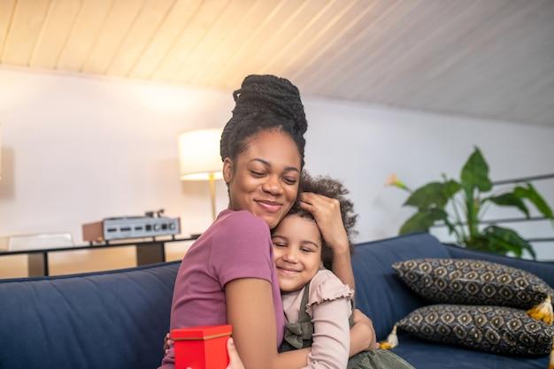 Jovem mãe feliz, de pele escura, com uma filhinha fofa e um presente abraçando com os olhos fechados