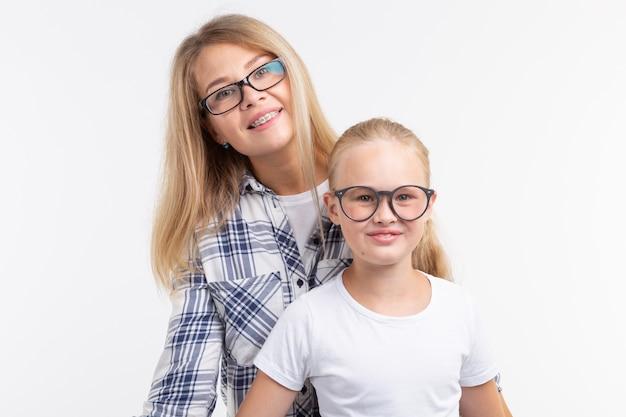 Jovem mãe feliz e criança rindo em óculos da moda se divertir na parede branca
