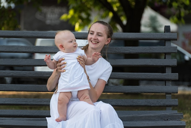 Jovem mãe feliz e sorridente com um bebê sentado no banco