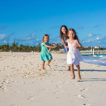 Jovem mãe feliz e suas adoráveis filhas se divertindo na praia exótica em dia ensolarado