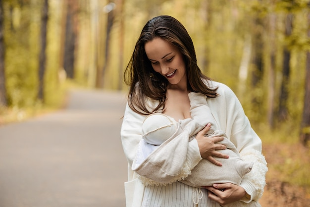 Jovem mãe feliz em jaqueta branca, mulher com bebê recém-nascido nos braços na floresta