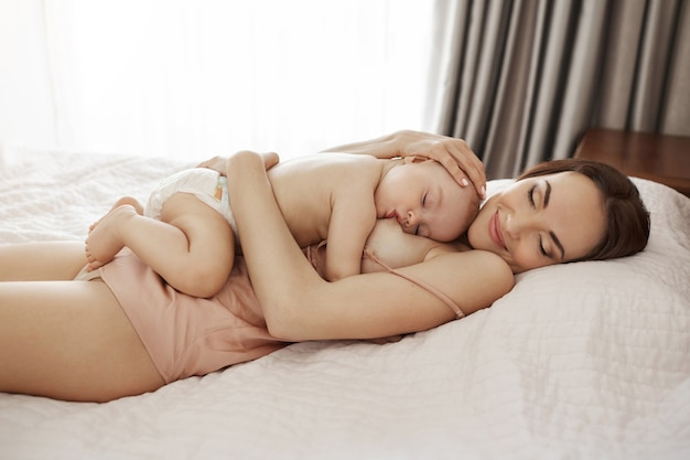 Jovem mãe feliz linda amamentando abraçando seu bebê deitado na cama em casa