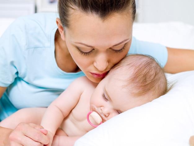 Jovem mãe feliz perto de recém-nascido dormindo