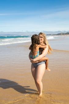 Jovem mãe feliz segurando a filha nos braços, carregando a criança, andando até os tornozelos na água na praia