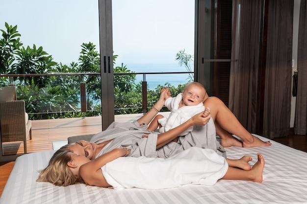 Jovem mãe feliz segurando seu adorável filho brincando na cama branca ao lado da filha mais velha, curtindo a manhã ensolarada em um moderno quarto de casa