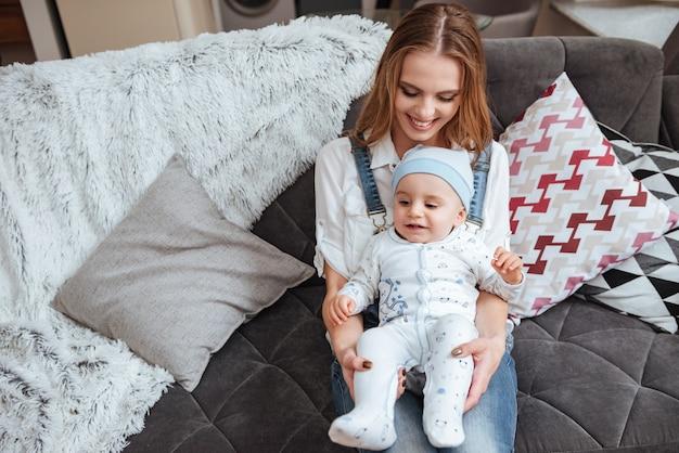Jovem mãe feliz sentada no sofá com o filho pequeno em casa