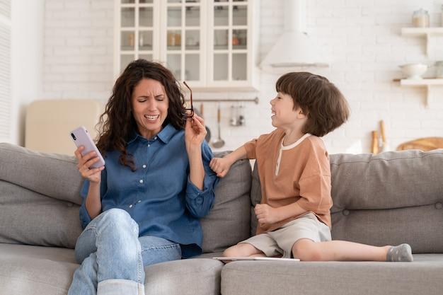 Jovem mãe frustrada cansada de filho pequeno desobediente hiperativo distrair do trabalho em smartphone