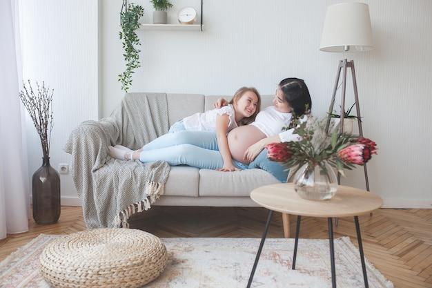 Jovem mãe grávida e sua filha dentro de casa.