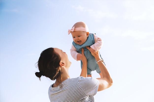 Jovem mãe joga bebê no céu, verão ao ar livre. mãe feliz e uma linda menina sorridente