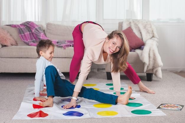 Jovem mãe jogando twister com seu filho. família alegre dentro de casa. família feliz tocando juntos