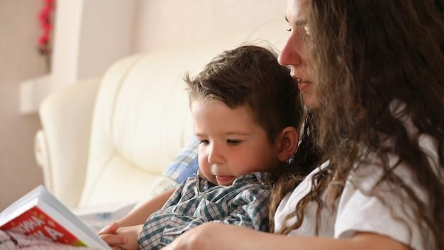 Jovem mãe lê um livro para o filho antes de dormir.