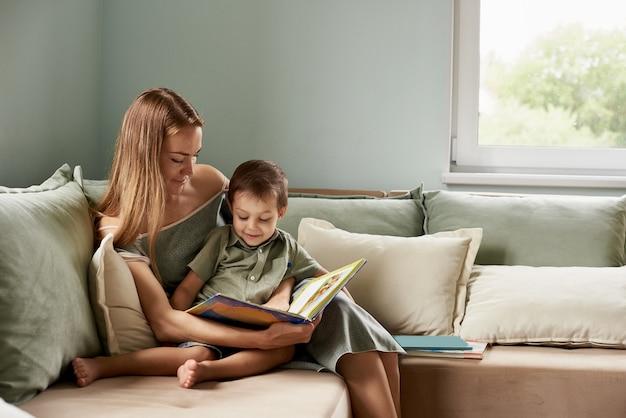 Jovem mãe, leia um livro para seu filho, menino na sala de estar de sua casa, raios de sol passando pela janela