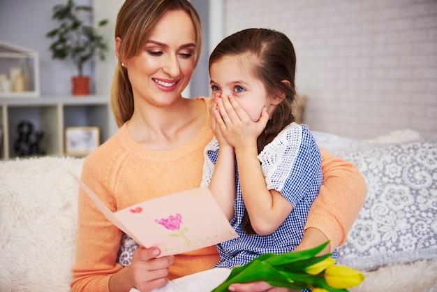 Jovem mãe lendo cartão de felicitações para o dia das mães